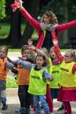 年轻小学生和他们的老师在一个公园做体育运动 图库摄影