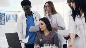 年轻小组医生在医院使用一台膝上型计算机,在会议期间的纸张文件 队多种族 影视素材