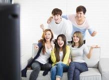 年轻小组坐看电视的沙发 免版税库存图片