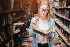 年轻少年在公立图书馆 她找到一本书并且读了它 这个女孩是镇静平安和体贴的 库存照片