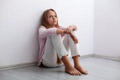 年轻少年女孩坐地板由墙壁-看a 免版税库存图片