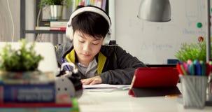 年轻少年学生听到音乐从片剂计算机和在家做家庭作业,左到右移动式摄影车的移动 股票视频