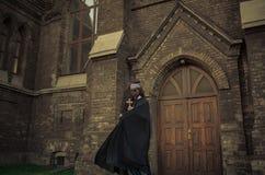 年轻尼姑是站立和祈祷与十字架在她的在tem的手上 图库摄影