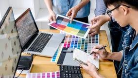 年轻工作在颜色选择和画在图形输入板的同事创造性的图表设计师队在工作场所,颜色 免版税库存图片