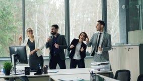 年轻工友快乐的队在现代笑办公室佩带的衣服移动的胳膊和的身体跳舞微笑和 股票视频