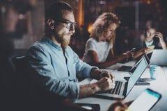 年轻工友队在夜办公室  使用电子小配件的青年人在桌 水平 免版税库存图片