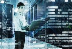 年轻工程师在数据中心里屋子与一台膝上型计算机的在手中在夜摩天大楼背景  概念的大 免版税图库摄影