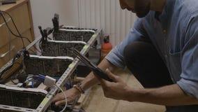 年轻工程师监视温度和检查连接在cryptocurrency开采的船具使用软件在个人计算机片剂- 影视素材