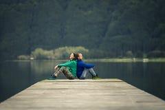 年轻已婚夫妇坐码头由火山的湖 免版税库存图片