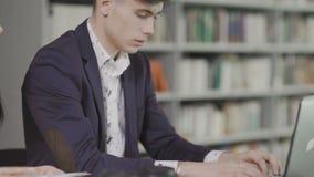 年轻帅哥并且工作坐膝上型计算机在图书馆里 咖啡在桌上的 股票录像