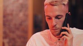 年轻帅哥谈话在夜咖啡馆的智能手机 坐在霓虹标志和饮用的鸡尾酒附近的他 股票视频