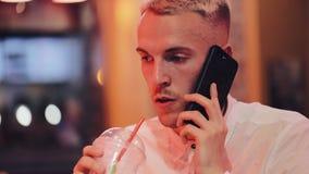 年轻帅哥谈话在夜咖啡馆的智能手机 坐在霓虹标志和饮用的鸡尾酒附近的他 影视素材