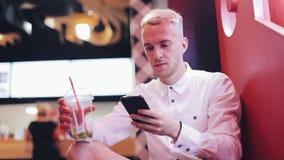 年轻帅哥谈话在夜咖啡馆的智能手机 坐在霓虹标志和饮用的鸡尾酒附近的他 股票录像