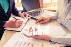 年轻帐户经理乘员组工作和谈论计划财政图表数据在办公室 库存照片