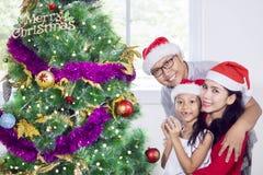 年轻庆祝圣诞节的父母和他们的女儿 免版税库存图片