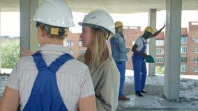 年轻建筑学和女工谈话在露天建造场所 免版税库存照片