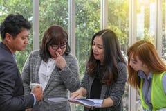年轻建筑队在工作 办公室工作者观察文件 库存照片