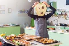 年轻微小的白种人妇女烘烤在获得的厨房里拿着在她的面孔前面的乐趣面团面具 图库摄影