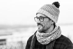 年轻微笑的人外形画象玻璃和法绒夹克的 被编织的帽子和皮屑 库存照片