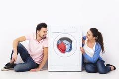年轻微笑的加上一台洗衣机,在白色背景 库存图片