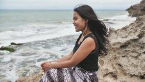 年轻微笑的印度尼西亚女孩在石海滩背景摆在 慢的行动 股票视频