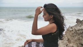 年轻微笑的印度尼西亚女孩在石海滩背景摆在 t 股票录像