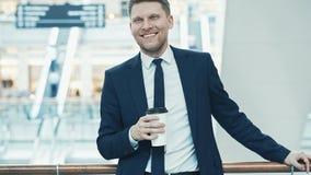 年轻微笑的商人用咖啡 库存照片