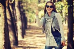 年轻微笑的女孩在有赞许的秋天公园 库存图片