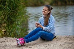 年轻微笑的妇女在与电话的优秀精神上和听到音乐 免版税库存照片