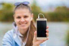年轻微笑的妇女在与电话的优秀精神上和听到音乐 库存照片