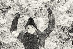 年轻微笑的妇女在多雪的针叶树下,无色 免版税库存图片