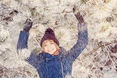 年轻微笑的妇女在多雪的针叶树下,秀丽filt 免版税图库摄影