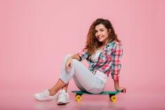 年轻微笑的妇女坐被隔绝的滑板 库存照片