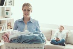 年轻微笑的妇女拿着干净的衣裳篮子  库存照片