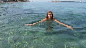 年轻微笑的妇女无危险游泳蛙泳干净的蓝色海 股票录像