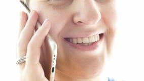 年轻微笑的妇女极端特写镜头照片谈话由手机 免版税图库摄影