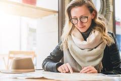 年轻微笑的妇女游人在咖啡馆坐在桌上在窗口附近和寻找在地图的一个方式 旅游业,旅行,假期 免版税库存图片
