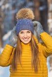 年轻微笑的妇女画象的明亮的衣裳在冬天森林里接触一个被编织的帽子 免版税库存图片