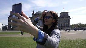 年轻微笑的妇女自画象智能手机增进柏林关闭的Reichstag 影视素材