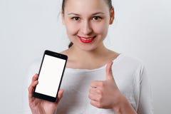 年轻微笑的妇女藏品智能手机垂直与白色屏幕和有copyspace的空间的 显示其他的姿态 库存图片