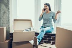 年轻微笑的妇女谈话在电话在箱子旁边 免版税图库摄影