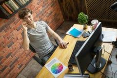 年轻微笑的数字艺术家设计师谈话由有他的顾客的智能手机在他的工作场所在顶楼样式办公室 库存照片