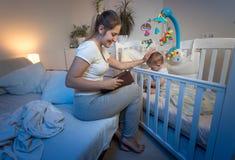 年轻微笑的母亲画象睡衣的坐床和阅读书对她的小儿子在去前睡 库存照片
