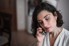 年轻微笑的深色的妇女在家谈话在电话 垂直的照片 库存图片
