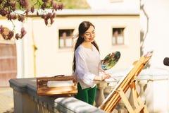 年轻微笑的深色的妇女艺术家在木兰附近一棵美丽的树绘在街道上的一幅画, 库存照片