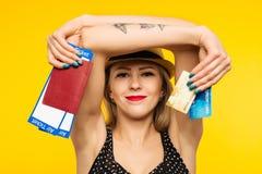年轻微笑的激动的女学生藏品护照登机牌票和在黄色背景隔绝的信用卡 图库摄影