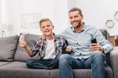 年轻微笑的男孩拿着gamepad和坐长沙发 免版税库存图片