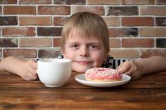 年轻微笑的男孩用桃红色多福饼和茶 库存照片