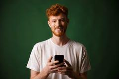 年轻微笑的红头发人有胡子的年轻人,听的m画象  免版税图库摄影