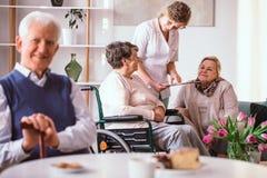 年轻志愿者谈话与轮椅的年长夫人在养老院 免版税库存照片